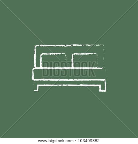 Sofa hand drawn in chalk on a blackboard vector white icon isolated on a green background.