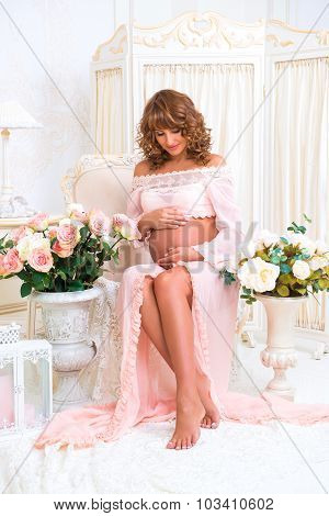 Redheaded Pregnant Woman Sits On Chair And Looks At Belly With Love