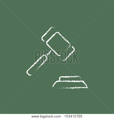 Auction gavel hand drawn in chalk on a blackboard vector white icon isolated on a green background.