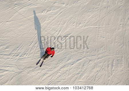 Aerial view of man skiing, wearing red jacket