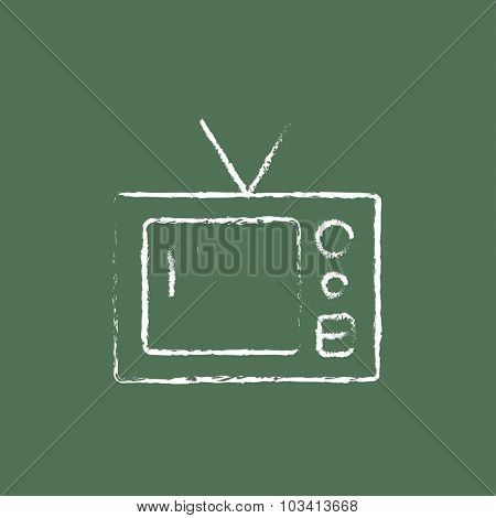 Retro television hand drawn in chalk on a blackboard vector white icon isolated on a green background.