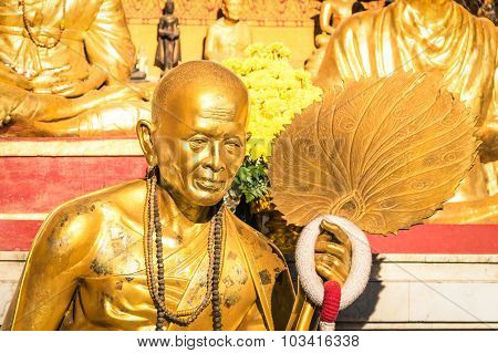 Golden Statue Of Old Buddhist Monk With Flowers Ring In The Sanctuary Of Doi Suthep - Ancient Buddha