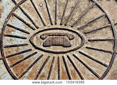 Telephone Symbol Icon On Rusty Manhole Cover.