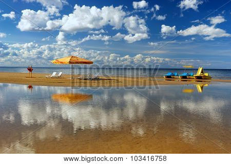 Hammock With An Umbrella And Chair On The Beach With Reflection