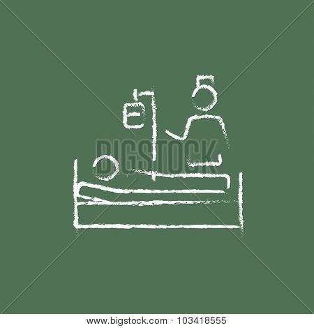 Nurse attending a patient hand drawn in chalk on a blackboard vector white icon isolated on a green background.