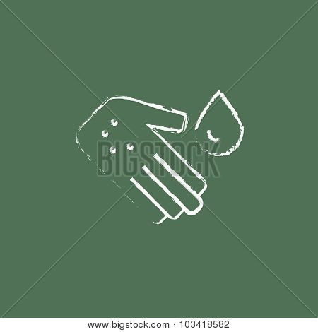 Microbes on the palm hand drawn in chalk on a blackboard vector white icon isolated on a green background.