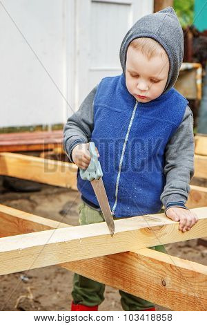 Little Studious Boy Sawing A Wooden Board. Home Construction. Little Helper.