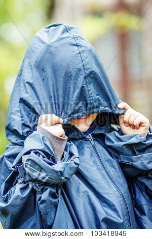 Funny Little Boy Walks In The Rain In A Raincoat With A Hood