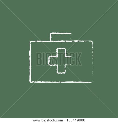 First aid kit hand drawn in chalk on a blackboard vector white icon isolated on a green background.