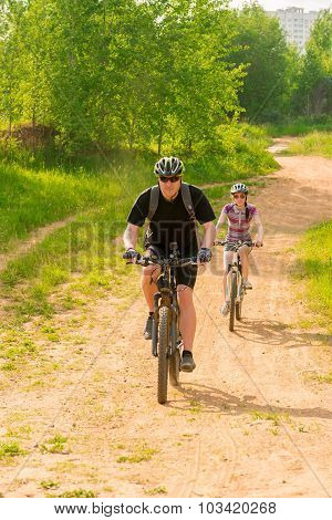 Bicycles Ride On A Country Road In Helmets