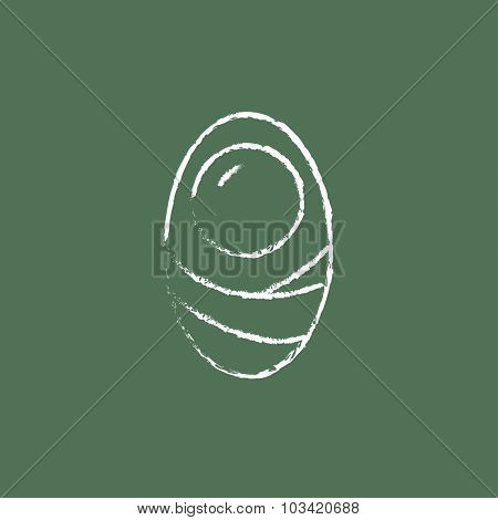 Infant wrapped in swaddling clothes hand drawn in chalk on a blackboard vector white icon isolated on a green background.