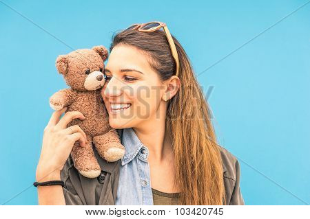 Young Woman With Small Vintage Teddy Bear On Her Shoulder On A Blue Wall Background