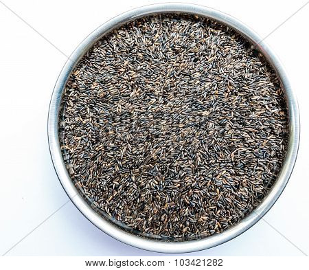 Indian niger seeds kept on a stainless steel bowl on a plain background