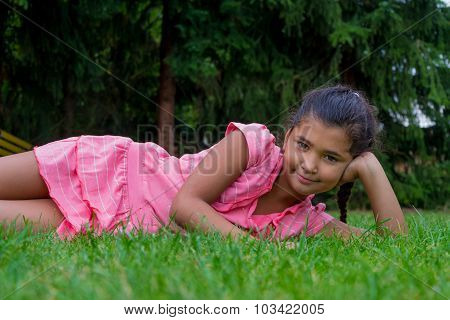 Small Gypsy Child Girl Lay Aside In Grass Smiling Happy Clothed In Dress