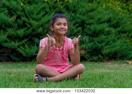 Little Child Gypsy Girl Showing Thumbs Up Sitting In Grass And Smiling