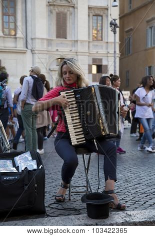 ROMA, ITALY-SEPT 24, 2015:  Woman playing accordion at Navonna place the biggest place in Roma which is a nice example of Baroque Roman architecture  in Roma, Italy