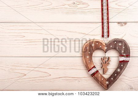 Christmas decorative wooden heart on the wooden background.