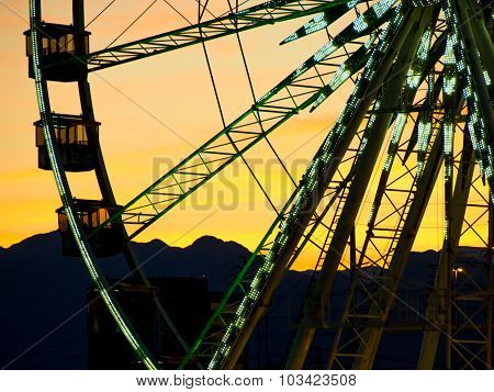 Detail And Silhouette Of Ferris Wheel With Sun Set