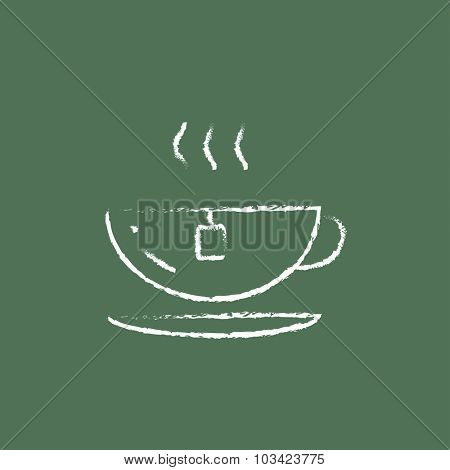 Hot tea in a cup hand drawn in chalk on a blackboard vector white icon isolated on a green background.