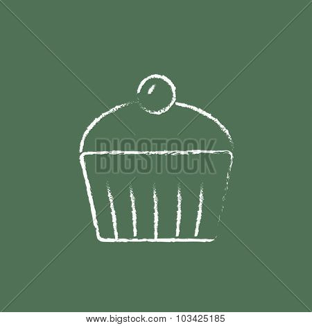 Cupcake with cherry hand drawn in chalk on a blackboard vector white icon isolated on a green background.