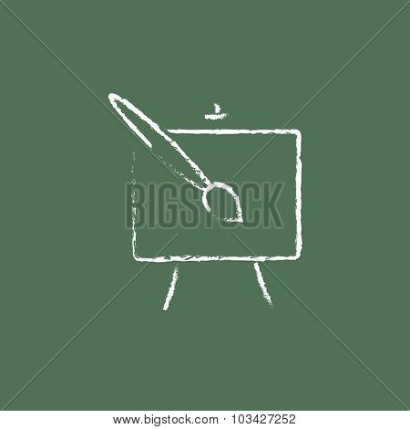 Easel and paint brush hand drawn in chalk on a blackboard vector white icon isolated on a green background.
