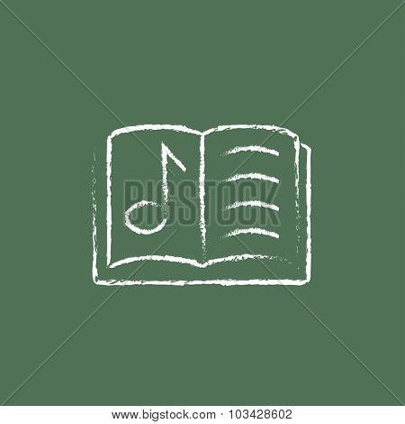 Music book hand drawn in chalk on a blackboard vector white icon isolated on a green background.
