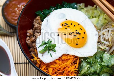 Korean cuisine, beef  Bibimbap in  a clay pot on wooden table
