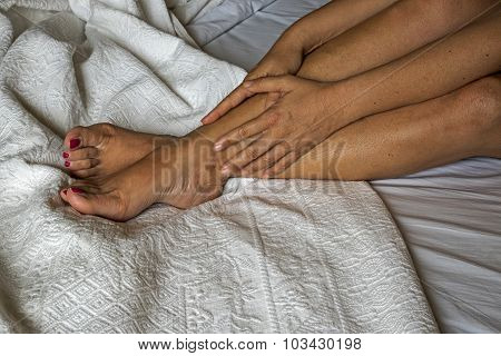 The woman massaging her legs on a bed