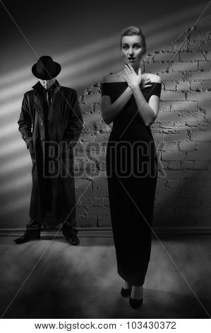 Woman In A Long Black Dress And A Man In A Raincoat And Hat
