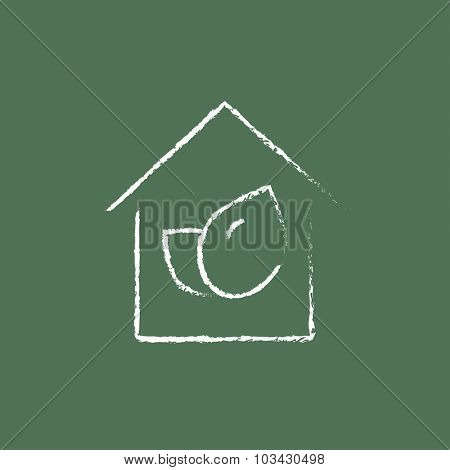 Eco-friendly house hand drawn in chalk on a blackboard vector white icon isolated on a green background.