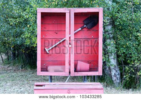 Red Fire Shield With A Shovel In A Forest