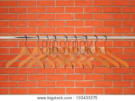 Wooden Clothes Hangers Over Orange Brick Wall
