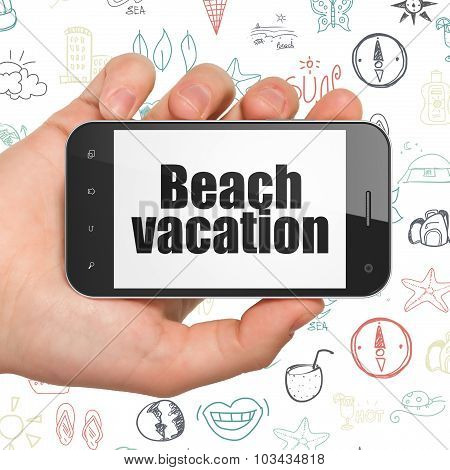 Tourism concept: Hand Holding Smartphone with Beach Vacation on display