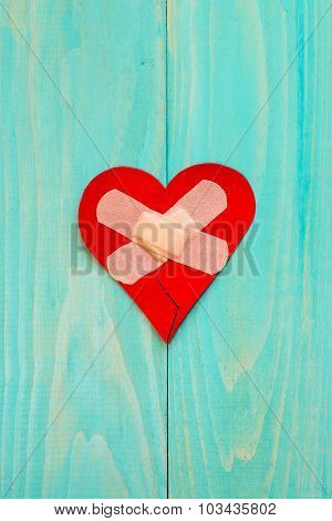 Plaster And Paper Broken Heart On Wooden Background