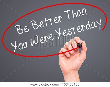 Man Hand writing Be Better Than You Were Yesterday with black marker on visual screen.