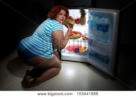 Photo at night of Overweight woman opening refrigerator and looking for a late supper