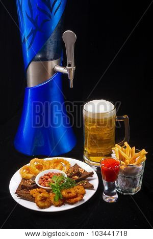 Beer barrel with beer glasses and Potatoes fries, Deep batter fried squid rings and  peanuts on dark background.