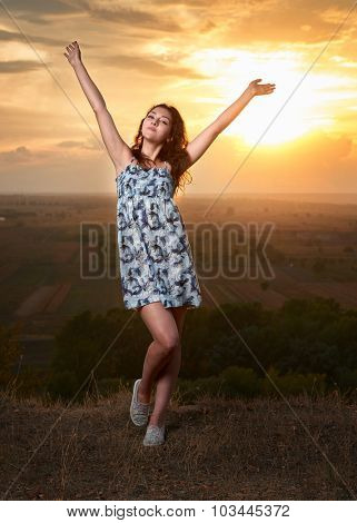 girl open arms at sunset on plain background