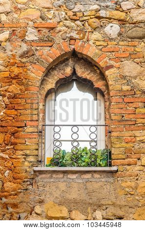 An old window decorated with flowers in italy