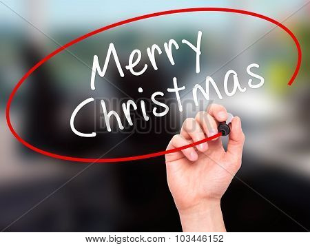 Man Hand writing Merry Christmas with black marker on visual screen.