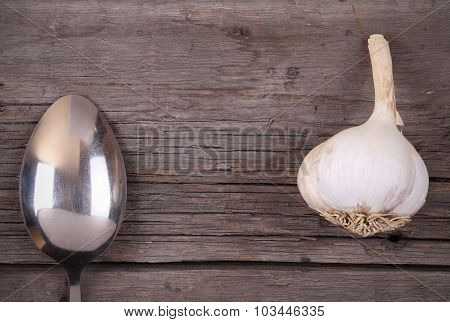 Spoon And Garlic On A Wooden Background