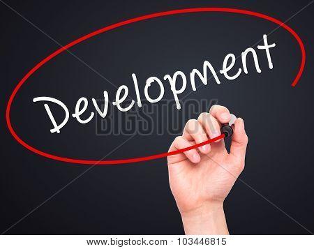 Man Hand writing Development with black marker on visual screen.