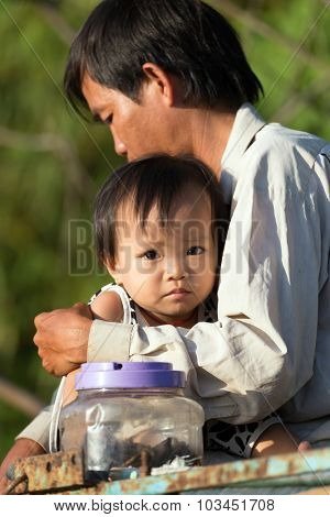 CAN THO, VIETNAM, DECEMBER 12, 2014 : A father is hugging his little daughter under the sunlight in the Phong Dien floating market in Can Tho, Vietnam