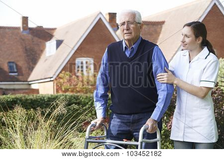 Carer Helping Senior Man To Walk In Garden Using Walking Frame