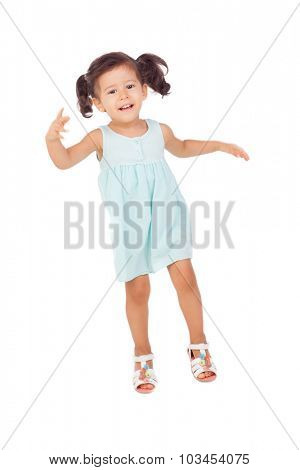 Funny little girl with pigtails jumping isolated on a white background