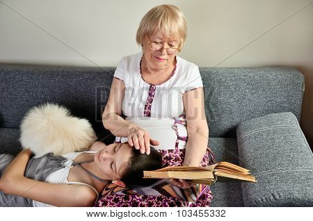 Granddaughter And Dog Lies Near Her Reading Grandmother