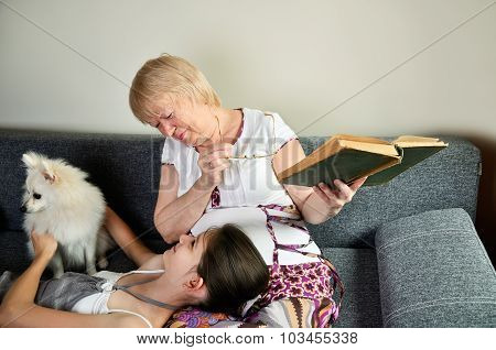 Grandmother And Granddaughter With The Dog Laughing Sit On The Couch And Looking At Each Other