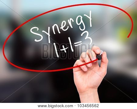 Man Hand writing Synergy concept 1+1=3 with black marker on visual screen.