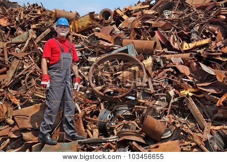 Recycling Industry, Worker Standing At Heap Of Old Metal
