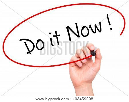 Man Hand writing Do it Now with black marker on visual screen.
